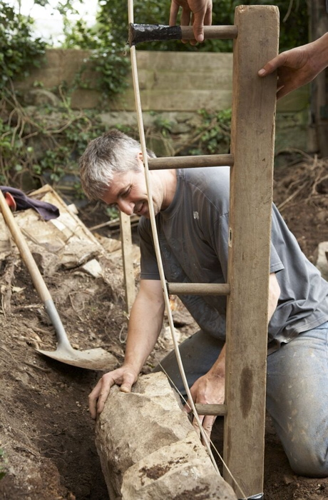 Guild apprentice with the tools of the trade - the traditional Cornish shovel and profile former setting the curved batter to the face of the hedge. Photo: Heritage Lottery Fund